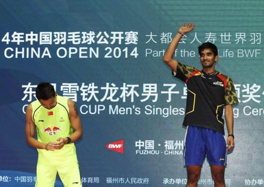 India's Kidambi Srikanth waves on the podium next to China's Lin Dan after he won the men's singles final against Lin at Badminton China Open in Fuzhou